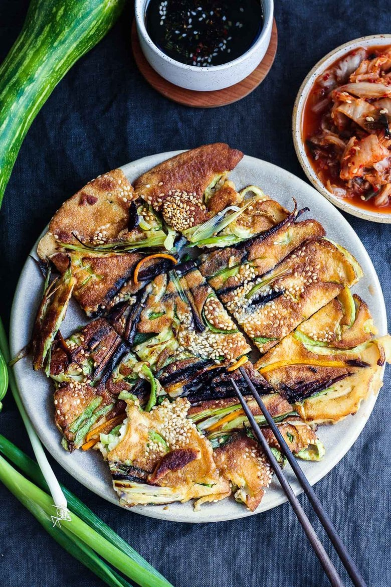 These Korean-inspired Zucchini Scallion Pancakes are a simple tasty treat! No-fuss preparation and ready to serve in minutes. Packed with zucchini and scallions, held together with rice flour and eggs, heavy on the veggies. Seasoned with gochujang pepper chili paste and a touch of rice wine, they are filled with savory flavor.