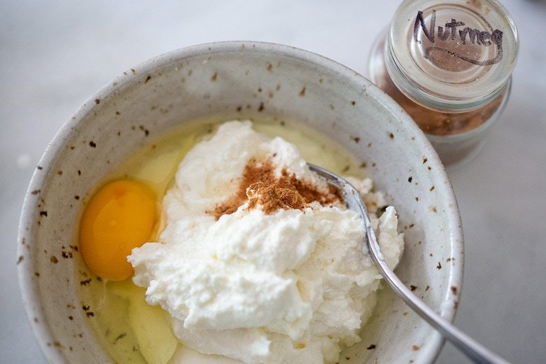 ricotta, nutmeg and and egg in a bowl about to be mixed.