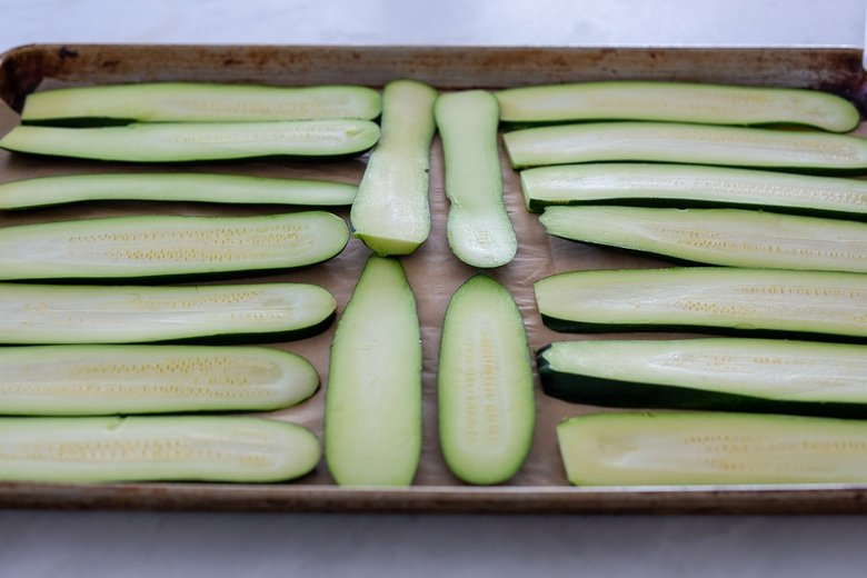 zucchini slices on a sheet pan, ready to roast or grill