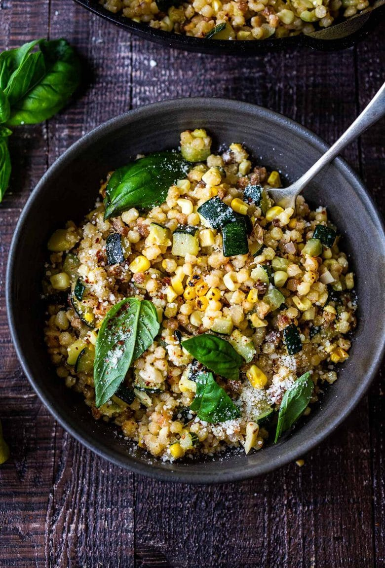 Fregola with Corn, Zucchini and Basil, sprinkled with pecorino. A fast and easy Italian-inspired meal that comes together in 30 minutes.