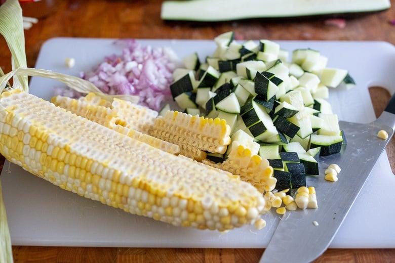 Chopped corn, shallot, garlic and corn on a cutting board.