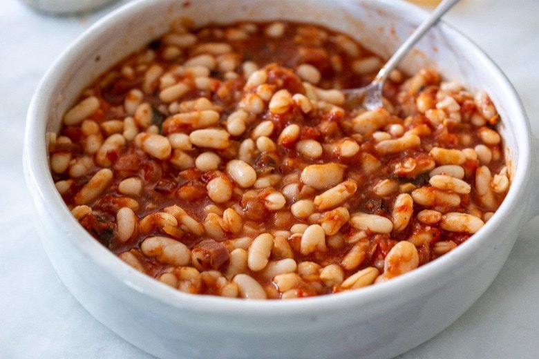 mixing in cannellini beans with the marinara sauce