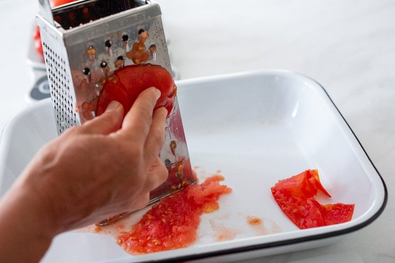 Grating the tomatoes on a grater