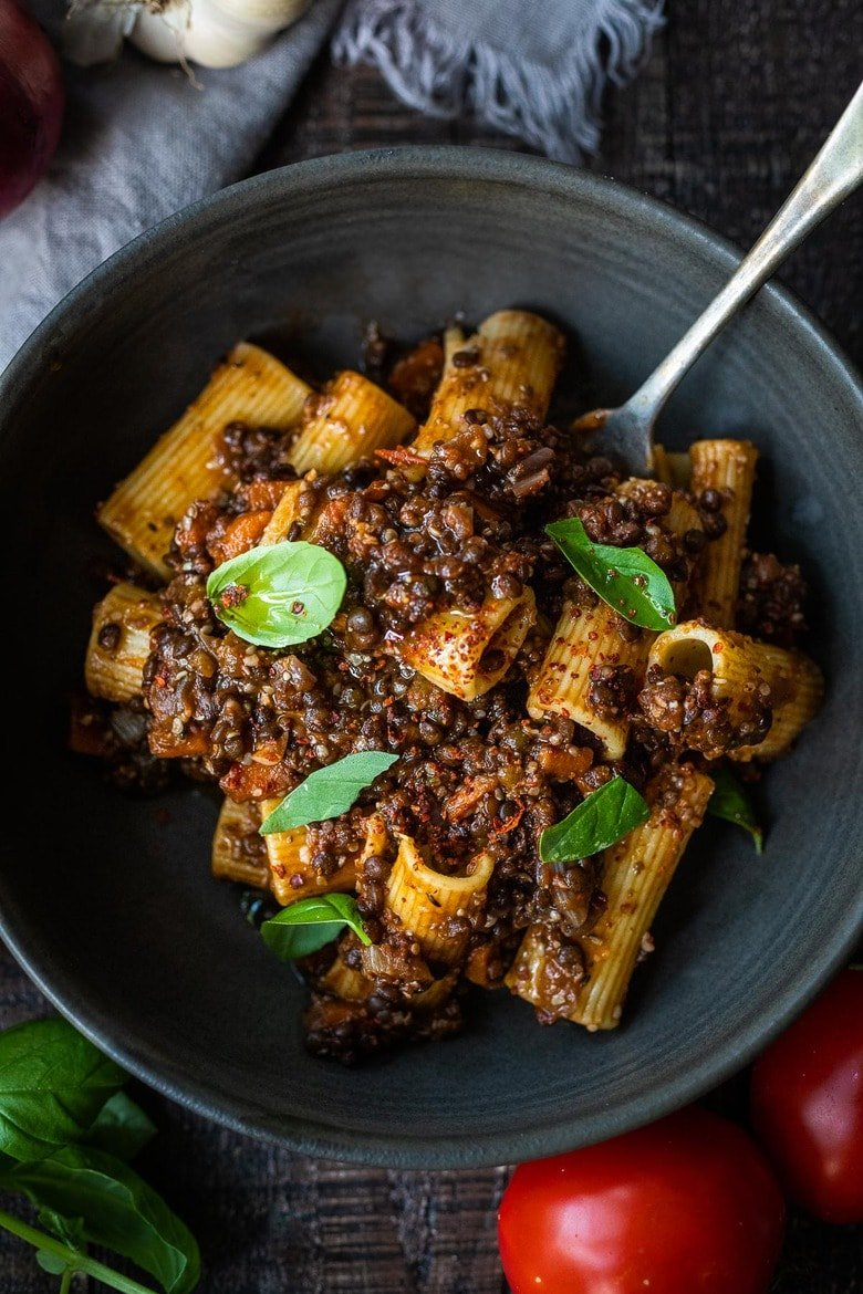 """Rich and robust, this plant-based Lentil Bolognese is hearty, """"meaty"""" and full of depth of flavor. Toss it with your favorite pasta, or spoon it over creamy polenta- either way, this simple nourishing vegan meal is one the whole family will enjoy."""