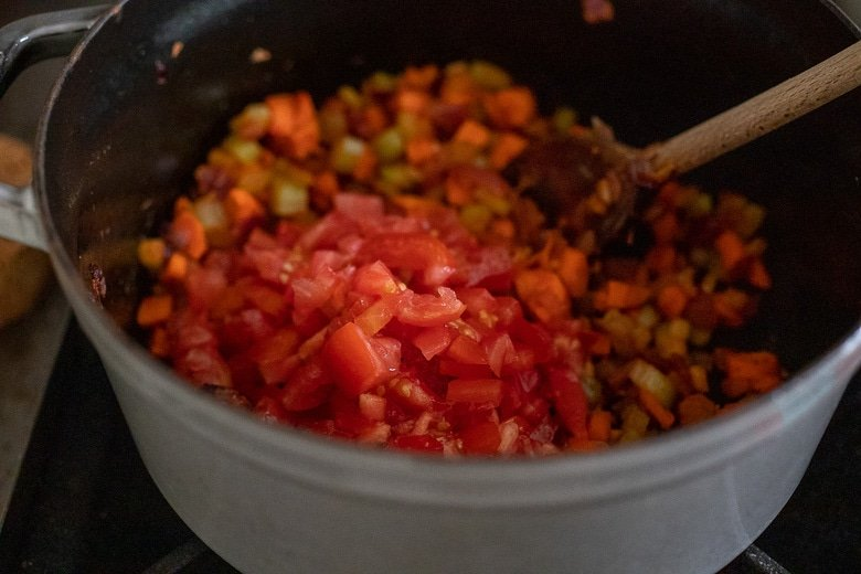 adding tomatoes to the bolognese